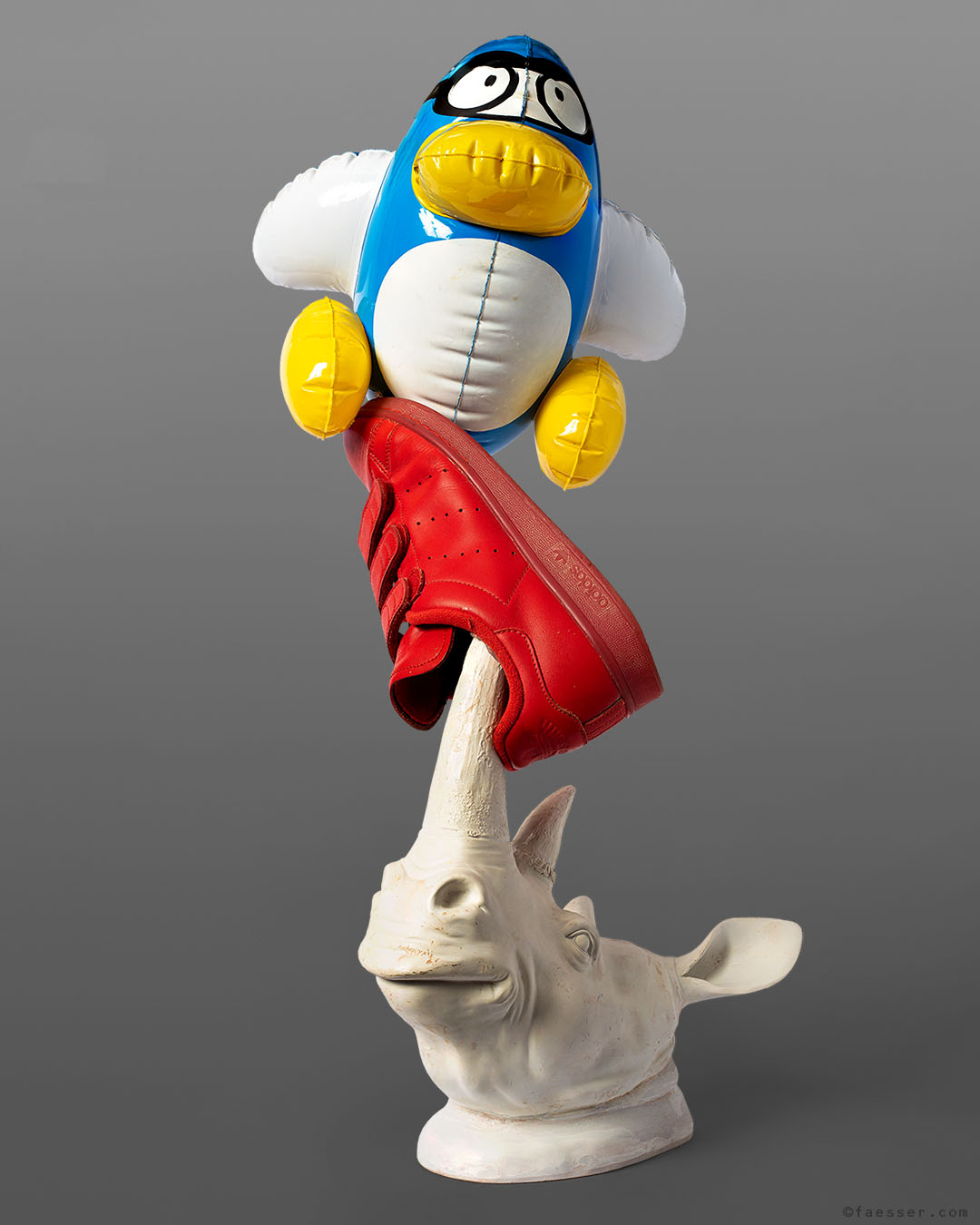 Rhinoceros head with Adidas Stan Smith sneaker and inflated comic figure; work of art as figurative sculpture; artist Roland Faesser, sculptor and painter 2019